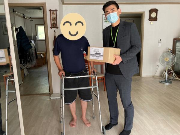장애인 집에 방문하여 물품을 전달해주는 사진