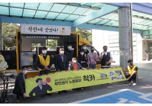 10명의 사람들이 야외에 있는 푸드트럭 앞에서 플랜카드를 들고 포즈를 취하고 있는 사진