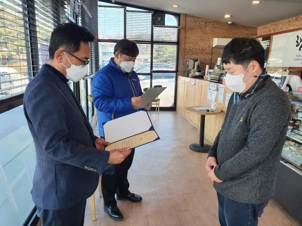 윤동인관장님이 카페직원 강현종씨에게 감사장을 수여하고 있고 김성빈팀장이 감사장 내용을 대독하고 있습니다.